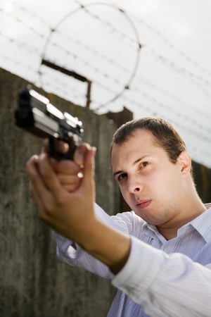 young man aiming a black gun against the prison wall Stock Photo - 7704683