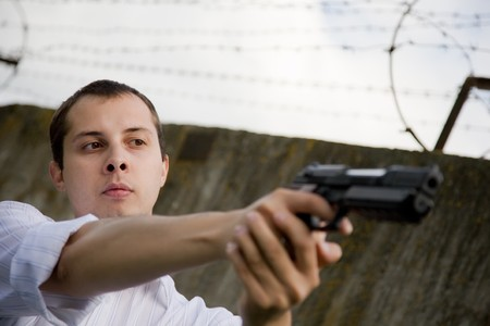 young man aiming a black gun against the prison wall Stock Photo - 7704738