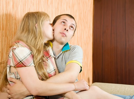 Young couple in love sitting on the couch kissing photo