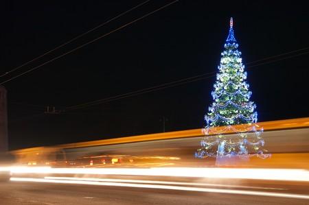 abetos: tráfico en la carretera de noche contra iluminada de árboles de Navidad en la ciudad de noche