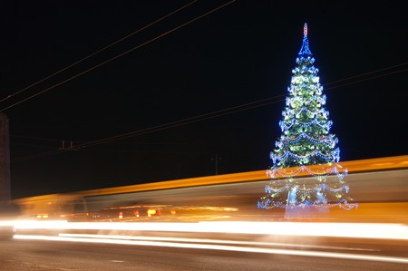 winter road: traffic on night road against  illuminated  Christmas tree at night city Stock Photo