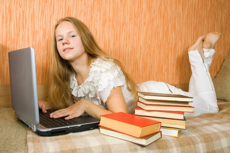 pretty young girl  with laptop and books on sofa  photo