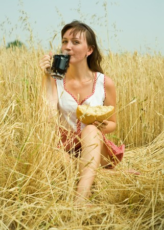 Girl  with quass and bread  at wheat field Stock Photo - 7705264