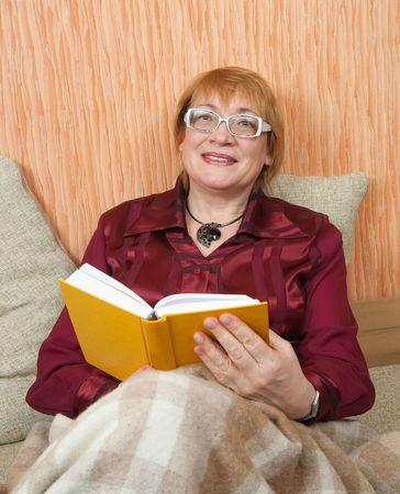 senior woman reading book on sofa at home photo