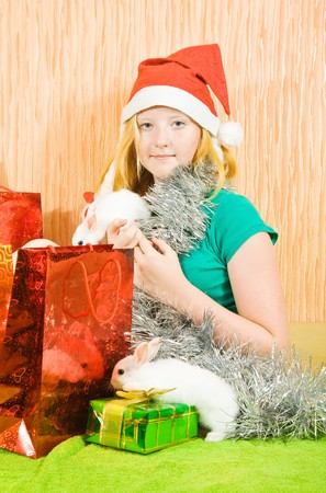 tawdry: new year  girl with two pet rabbits sitting in home  Stock Photo
