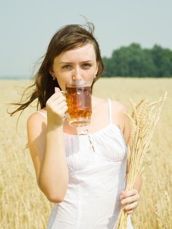 Girl  with beer and wheat ear  at cereals field photo