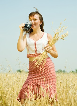 Girl  with quass and wheat ears  at wheat field Stock Photo - 7776654