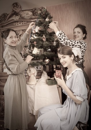 Retro photo of  daughters with mother decorating Christmas tree at home photo