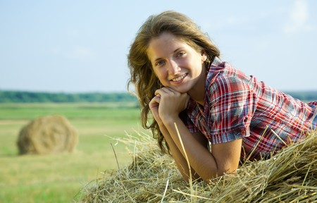 Young girl laying on top of a hay bail photo