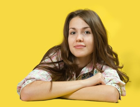 casualy: portrait of long-haired brunette girl over yellow