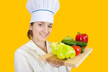 Portrait of female cook in  toque with  vegetables  over yellow  Stock Photo - 7776821