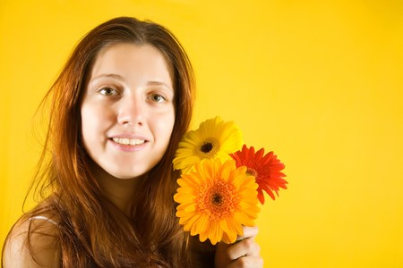 Portrait of  girl with flowers over yellow background photo