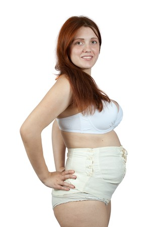 belly bandage: pregnant woman wearing obstetrical binder. Isolated over white Stock Photo