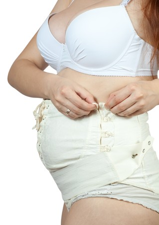 belly bandage:  Closeup of pregnant woman dressing maternity belt. Isolated over white