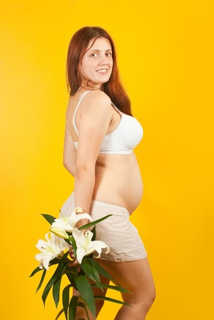 Portrait of 5 months pregnant woman over yellow photo