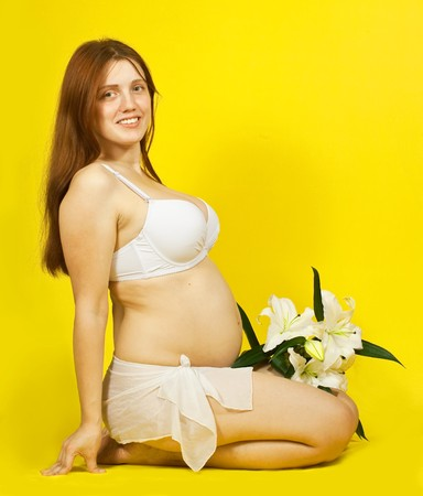 Sitting 5 months pregnant woman over yellow photo
