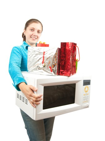 mini oven: Girl with microwave oven and present boxes. Isolated over white