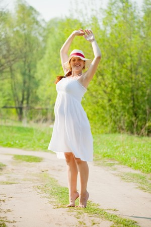 Portrait of 6 months pregnant woman on summer road photo