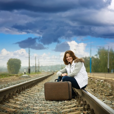 Girl on  railway sitting with her suitcase photo