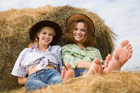 country girls restings on fresh hay bale Stock Photo - 7777684