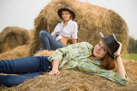 country girls laying on  hay bails in field Stock Photo - 7777675
