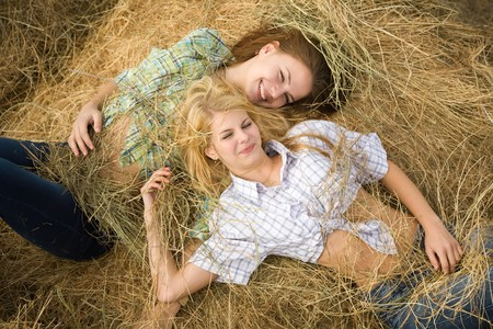 adolescence: country girls laying on  hay bail at farmland