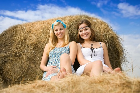 country girls resting on fresh hay bale photo