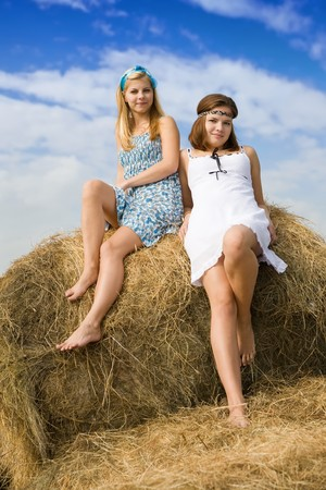 barn girls: Portrait of country girls on hay in summer Stock Photo