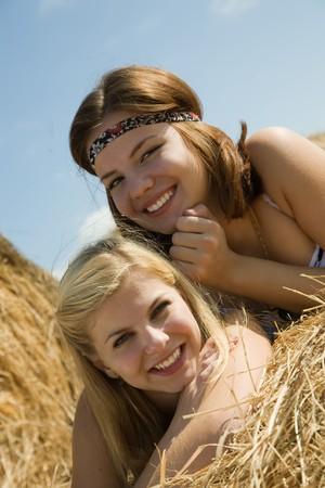 Happy girls on fresh hay at field Stock Photo - 7777660