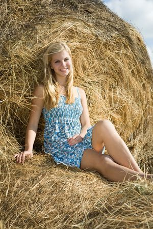 Pretty girl resting on fresh hay bale Stock Photo - 7777691