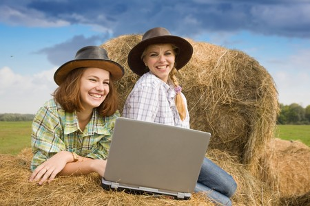 Two country girls with notebook on hay in farm photo