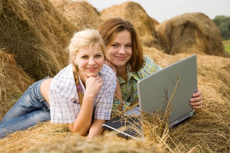 country girls with laptop on  hay at field photo