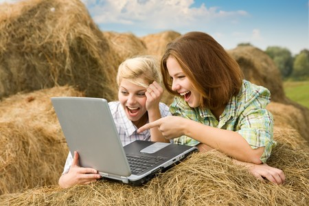 hay field: Happy country girls relaxing with laptop in farm