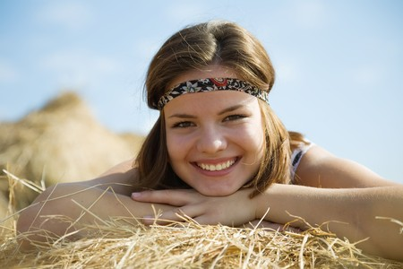 Young girl laying on top of straw bail photo