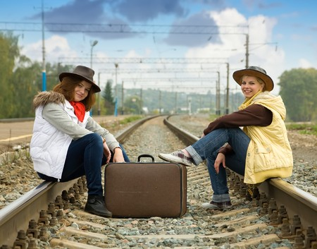 baggage train: Girls on  railway sitting with her suitcase