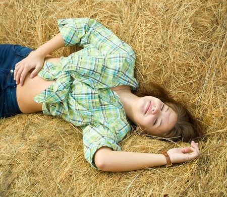 Pretty girl in checked shirt resting on straw bale photo
