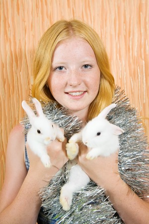 teen girl in peddlery  with two pet rabbits  photo