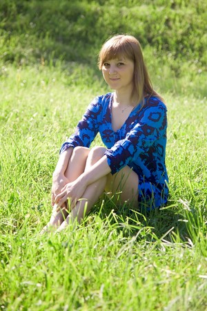 teener: teen girl in blue dress sitting on meadow Stock Photo