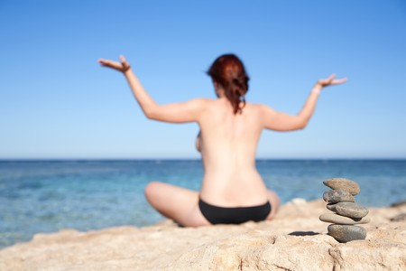 Balanced stones and  girl doing yoga against sea, Focus on stones photo