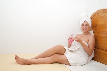 young woman in towel after shower  on her bed  photo