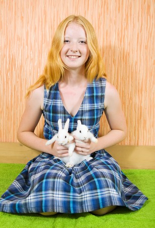 Teen  girl with two pet rabbits smiling indoor photo