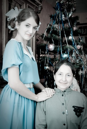 Retro portrait of daughter with mother against Christmas tree at home Stock Photo - 7873612