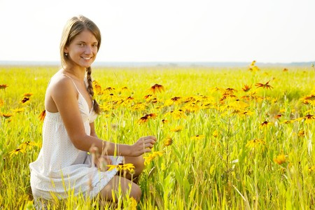 Portrait of  girl  sitting in flowers meadow photo