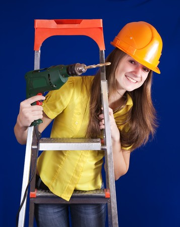 Female construction worker in a hard hat with drill near stepladder photo