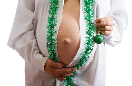 Closeup of Pregnant woman belly with christmas decorations