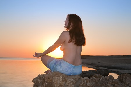 Topless girl  practicing yoga   against sunset of a sun at sea coast photo