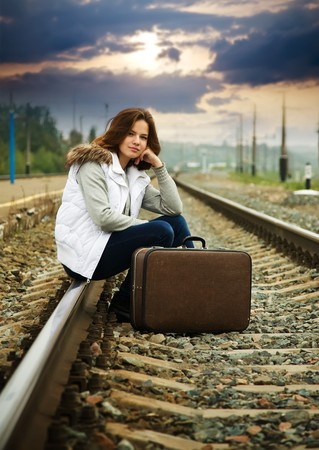 Sad girl on  railway sitting with her suitcase  photo