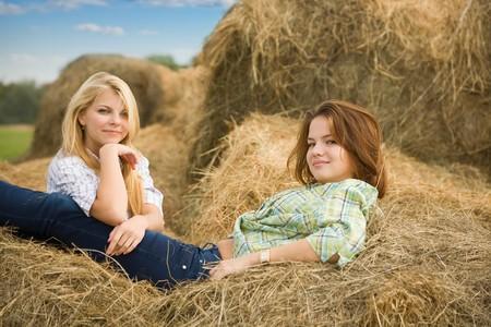 Farm girls on fresh hay at field photo