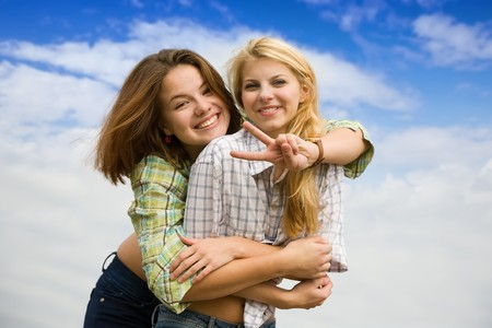 Two girls together against cloudy sky photo