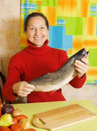 Mature woman with salmon fish in her kitchen photo